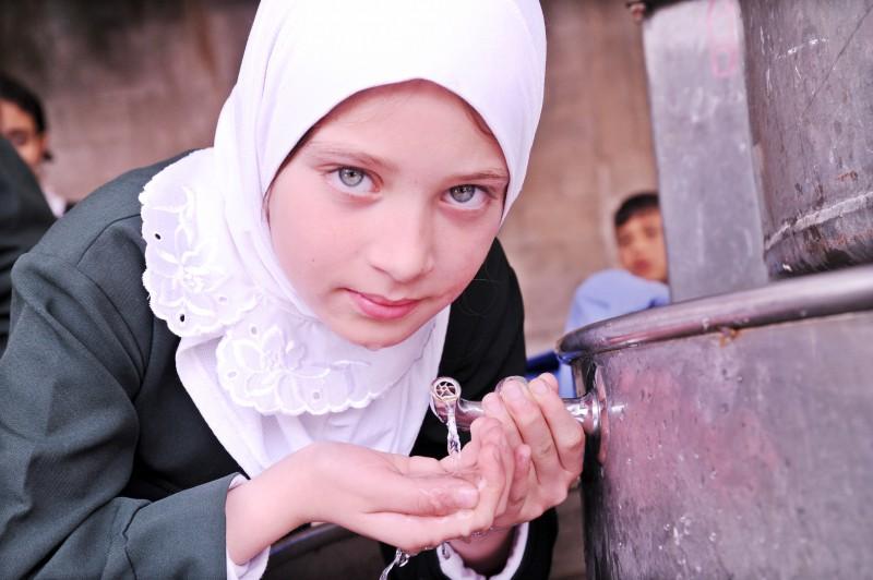 Gazan girl drinks from water fountain
