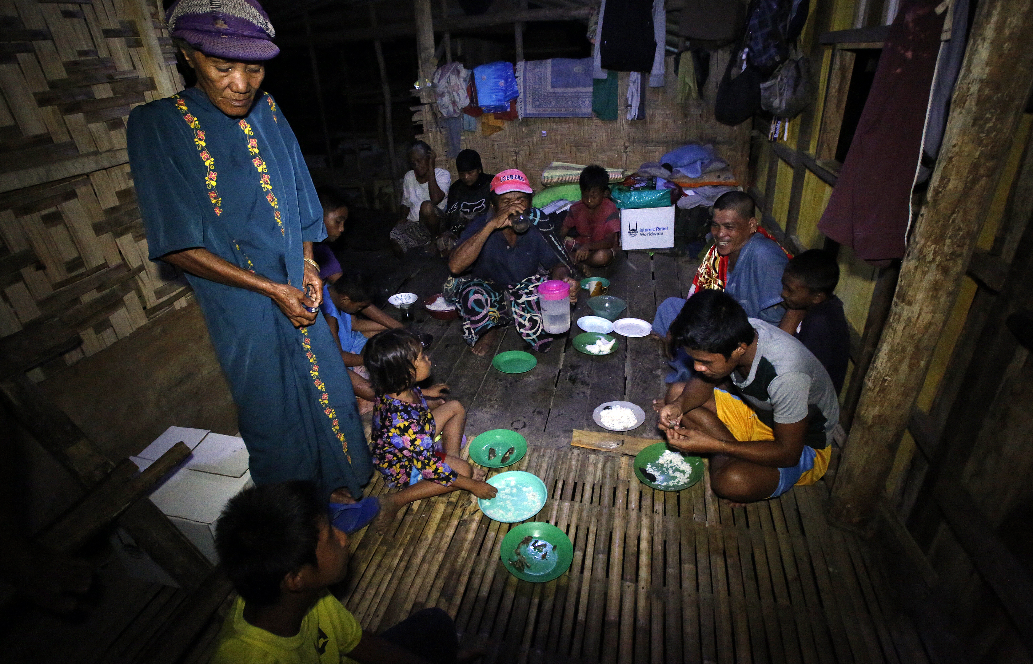 Imam Guiamed Nur sits with his neighbours in their community hut to break fast together.
