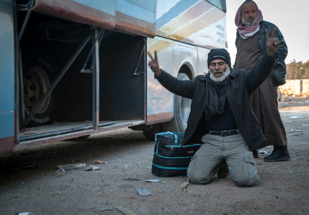 A man drops to the ground with a peace sign after being evacuated from Aleppo