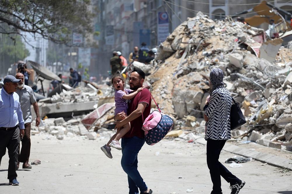 A family amid the rubble on Al Wahda street, Gaza.